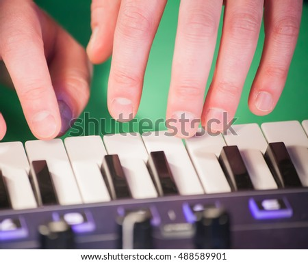 young hands of man playing synthesizer in studio