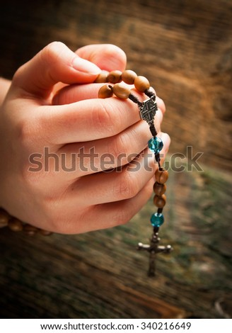 Young hands with wooden rosary  - stock photo