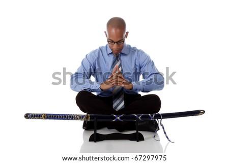 Young handsome African American businessman sitting cross legged praying  Japanese katana sword in front. Studio shot. White background. - stock photo