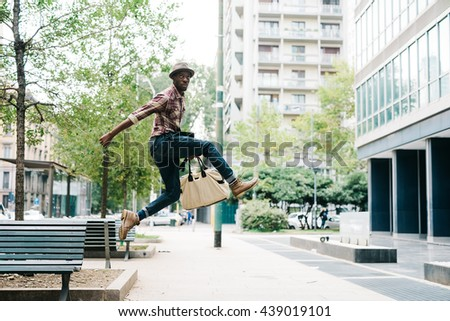Young handsome afro black man jumping in the street of the city, looking upward, holding a bag - jumping, having fun concept