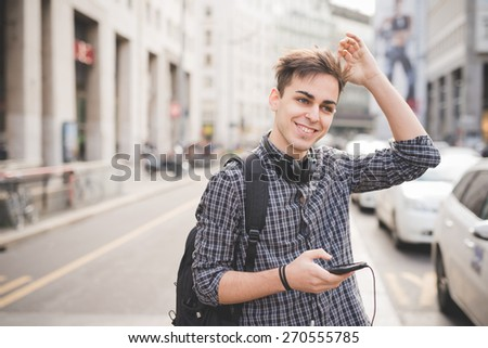 young handsome alternative dark model man in town listening to music with headphones and smartphone connected wireless - stock photo
