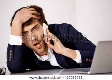 Young handsome angry businessman in suit talking on phone at the office sitting at the table looking at camera. - stock photo