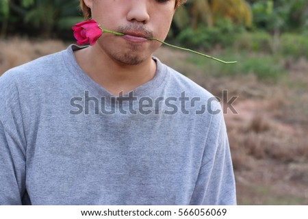 Young handsome asian man is holding a red rose in his mouth on nature blurred background.  Love and romance Valentine's day concept.