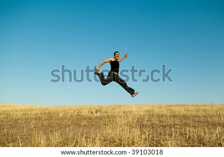 Young handsome asian man jumping joyfully in the barley meadows