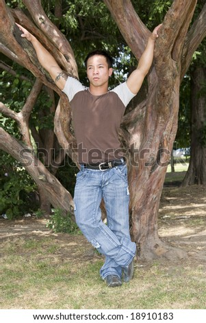 Young handsome Asian man standing by tree