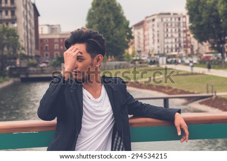 Young handsome Asian model dressed in black posing by an urban artificial basin - stock photo