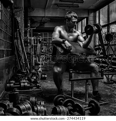 Young handsome athlete in old rusty gym - stock photo
