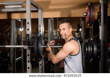 Young handsome athletic man training at gym hall