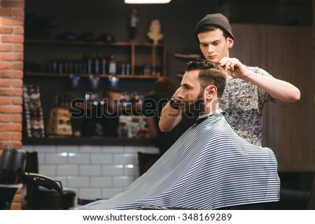 Young handsome barber making haircut of attractive bearded man in barbershop - stock photo
