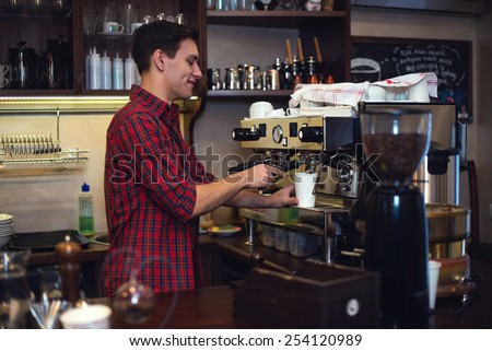 Young handsome barista hipster making coffee for his clients in the cafe