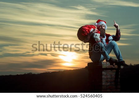 young handsome bearded bad santa claus man with long beard in checkered shirt jeans and red new year hat in christmas or xmas coat with toy sack on brick chimney in sunset, copy space