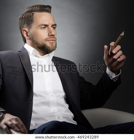 Young handsome bearded caucasian man sitting on chair with a cigar. Perfect skin and hairstyle. Wearing grey suit. Studio portrait on gradient black to grey background.