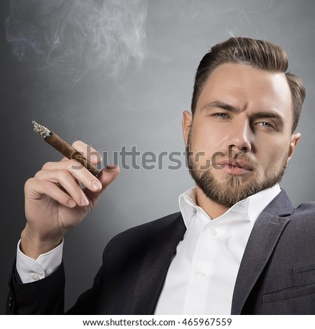 Young handsome bearded Caucasian man sitting on chair with cognac and a cigar. Perfect skin and hairstyle. Wearing suit and watch. Studio portrait on gradient black to grey background.