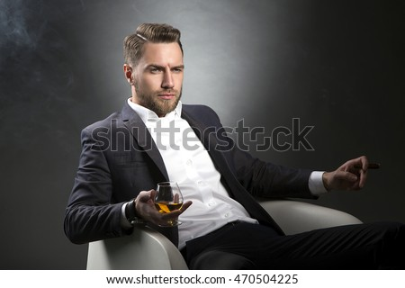 Young handsome bearded caucasian man sitting on chair with cognac and a cigar. Perfect skin and hairstyle. Wearing grey suit and watch. Studio portrait on gradient black to grey background.