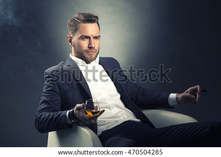 Young handsome bearded caucasian man sitting on chair with cognac and a cigar. Perfect skin and hairstyle. Wearing grey suit and watch. Studio portrait on gradient black to grey background. Toned