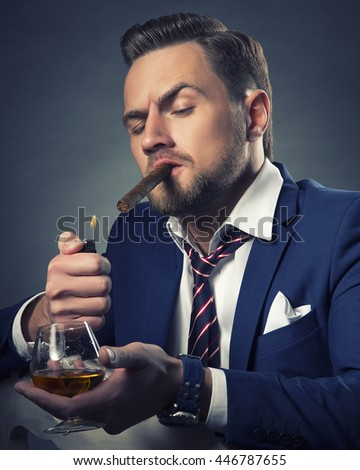 Young handsome bearded caucasian man sitting on chair with cognac and fire a cigar. Perfect skin and hairstyle. Wearing blue suit and watch. Studio portrait on gradient black to grey background. Toned