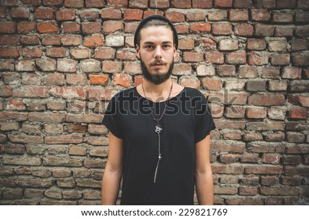 young handsome bearded hipster man in the city - stock photo