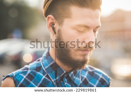young handsome bearded hipster man using smartphone and listening music with earphones in the city - stock photo