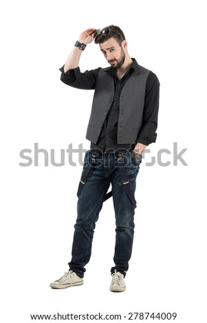 Young handsome bearded man putting sunglasses on his head looking at camera. Full body length portrait isolated over white background.