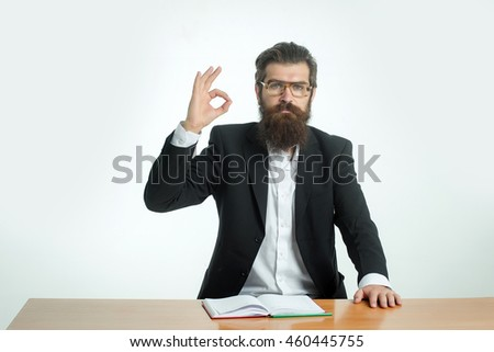young handsome bearded man scientist or professor with long beard and teacher glasses with book or notepaper sitting at table with okey gesture isolated on white background