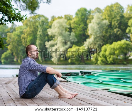 Young handsome bearded man sitting on wooden pier in summer day, meditating and relaxing - stock photo