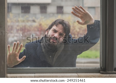 Young handsome bearded man with coat posing behind a glass in the city streets - stock photo