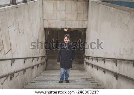 Young handsome bearded man with coat posing on stairs - stock photo