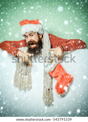 young handsome bearded santa claus man with long beard in red sweater and new year hat holds decorative christmas or xmas stocking or boot on white green background under snow, copy space