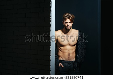 young handsome bearded sexy macho man with long beard and stylish hair in jacket and pants with muscular bare torso in studio on black and brick wall background, copy space