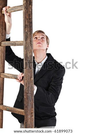 Young handsome blond man holds old wooden ladder and looks up - stock photo