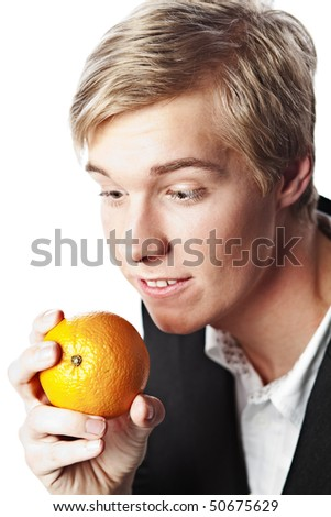 Young handsome blond man looks at orange in his hand with passionate desire - stock photo