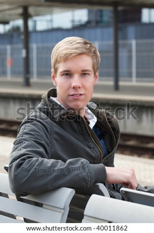 Young handsome blond man sitting on a bench on railway station