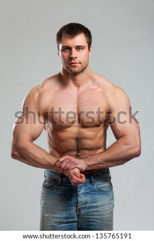 Young handsome bodybuilder isolated over grey background - stock photo