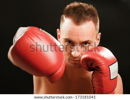 Young handsome boxer man isolated on black background