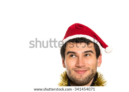 Young handsome brunette man wearing red hut smiling, happy, on white background with copy space, looking up