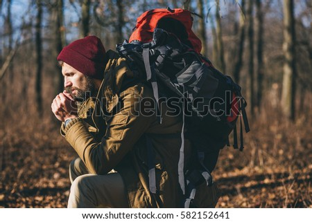 young handsome brutal bearded man traveling in the wild nature with touristic backpack, autumn style, warm coat, hat, traveler, adventure, free spirit, forest