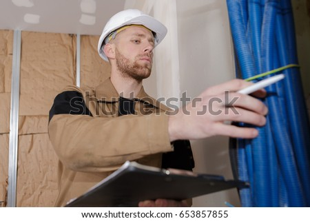 young handsome builder holding a clipboard
