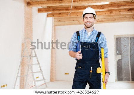 Young handsome builder standing and smiling at the working place indoors - stock photo