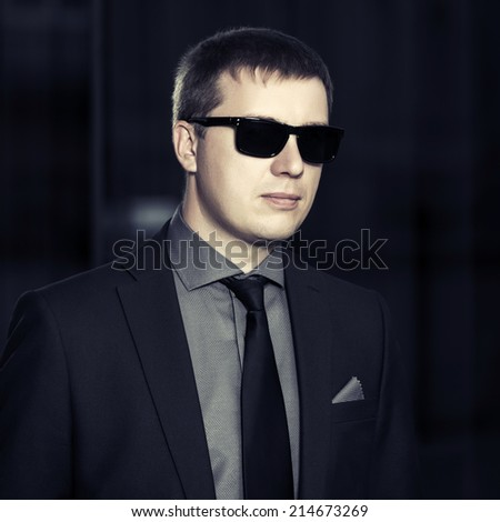 Young handsome business man against office building  - stock photo