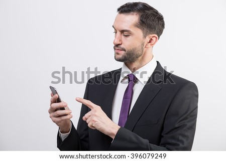 Young handsome business man checks his cellphone