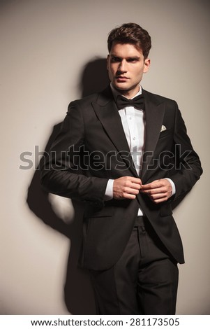 Young handsome business man closing his jacket while leaning on wall. - stock photo
