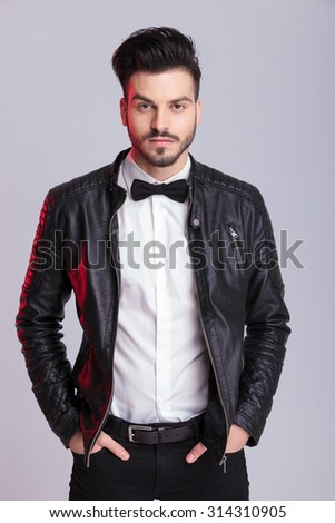 Young handsome business man holding his hands in pockets while posing on grey studio background.