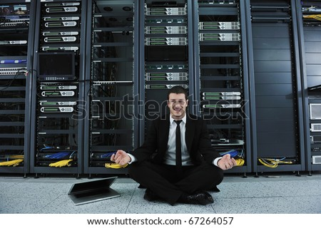 young handsome business man in black suit and tie practice yoga and relax at network server room while representing stres control concept