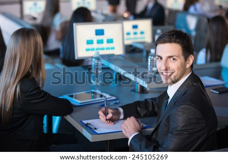 Young handsome business man is looking at the camera during presentation in modern conference hall.
