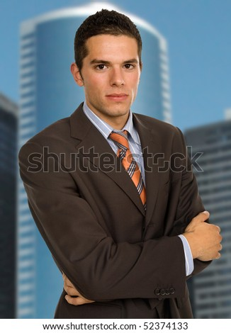 young handsome business man portrait with some office buildings behind