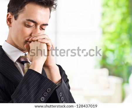 Young handsome business man praying - stock photo