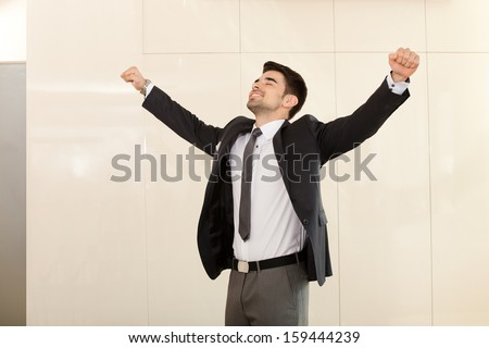 Young handsome business man smiling and celebrating an achievement with his arms risen and his fists clenched