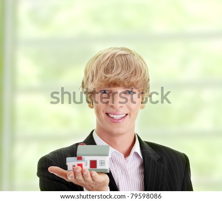 Young handsome business man with house model - real estate - stock photo