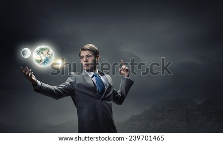 Young handsome businessman and Earth planet. Elements of this image are furnished by NASA