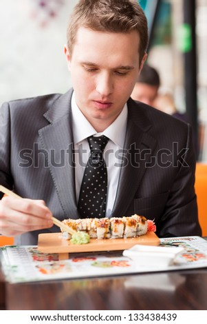 Young handsome businessman eating sushi with sticks in a cafe - stock photo